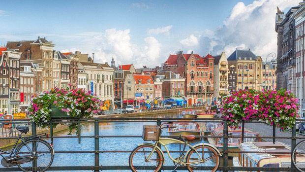 Case  si biciclete pe un pod peste un canal din Amster